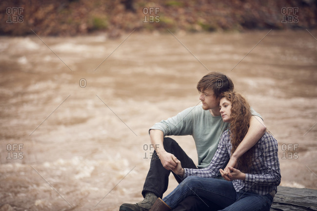 Couple peacefully sitting close by rural river