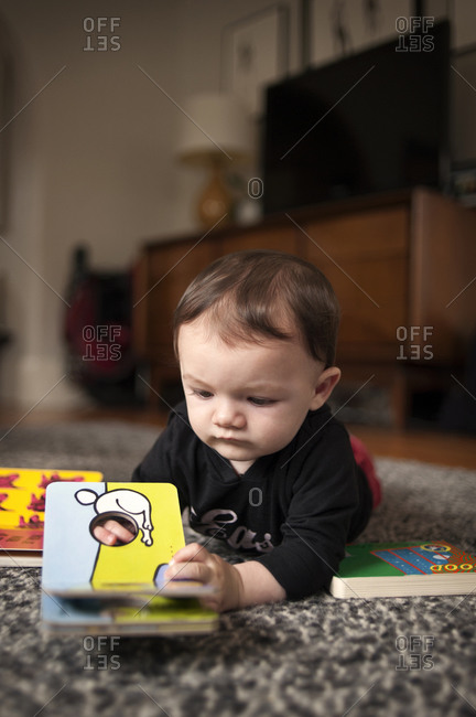 Toddler boy on floor with book