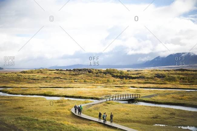 People walk along a footbridge in Thingvellir National Park in Iceland
