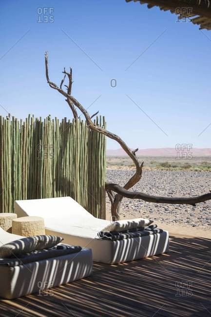 Lounge chairs by a private pool at a hotel in Sossusvlei, Namibia