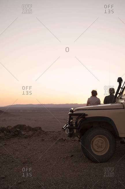 Two people watch the sunset on a cliff at Sossusvlei, Namibia