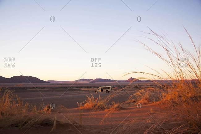 A safari van at sunrise in Sossusvlei, Namibia