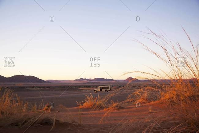 A safari van at sunrise in Sossusvlei, Namibia
