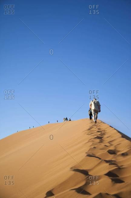A group of hikers climbs a dune in Sossusvlei, Namibia