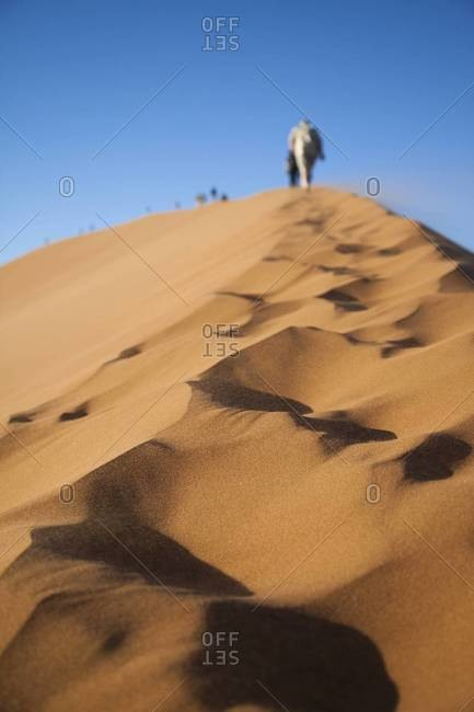 A group of hikers climbing a dune in Sossusvlei, Namibia