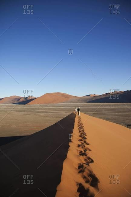 Hikers admire the view from a dune in Sossusvlei, Namibia