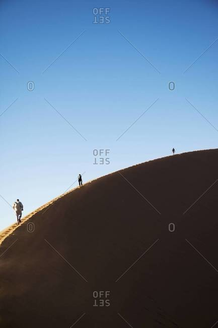Three hikers on the edge of a sand dune in Sossusvlei, Namibia