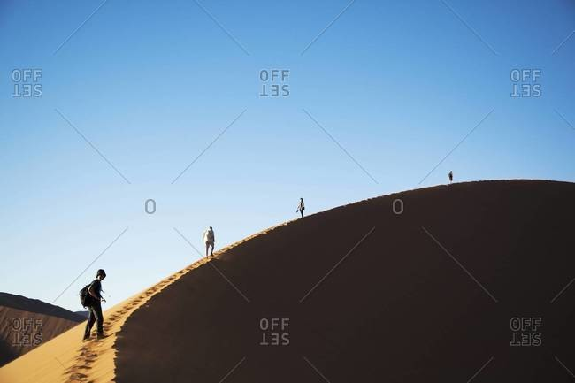 Hikers on the edge of a sand dune in Sossusvlei, Namibia