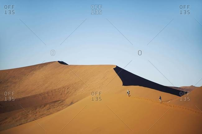 Hikers on a steep sand dune in Sossusvlei, Namibia