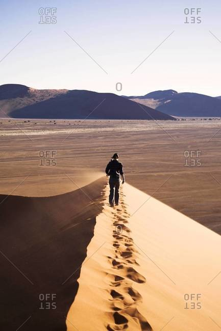 A woman hiking across a dune in Sossusvlei, Namibia