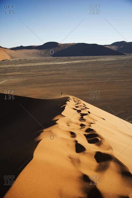 A person hiking across a dune in Sossusvlei, Namibia