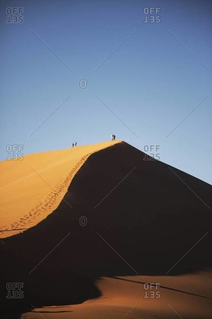 People walking at the top of a dune in Sossusvlei, Namibia