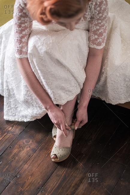 Bride buckling her shoes