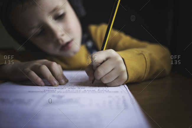 Young boy at table doing homework