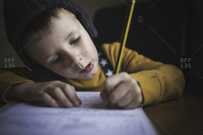 Young boy at table doing his homework