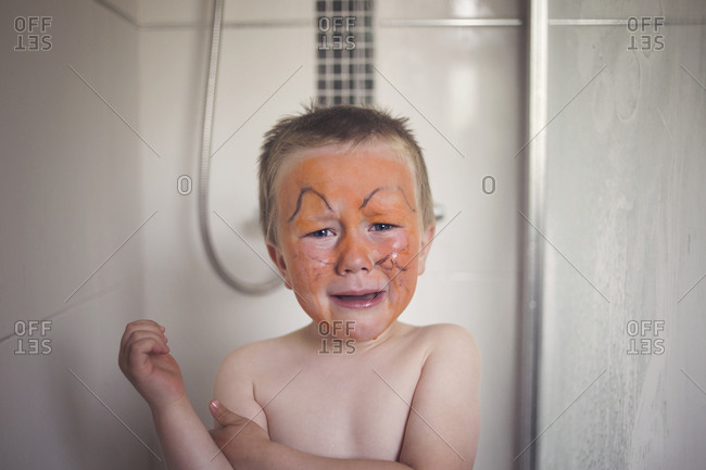 Upset boy in shower with face paint