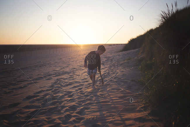 Boy dragging stick along beach