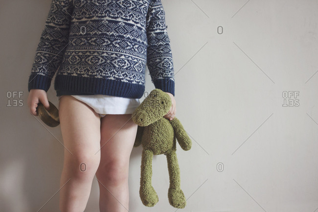 Boy in sweater and underwear holding doll