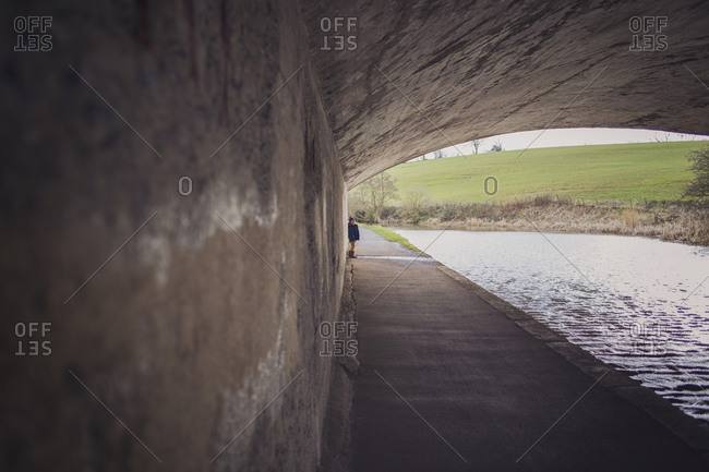 Boy walking on river path under bridge