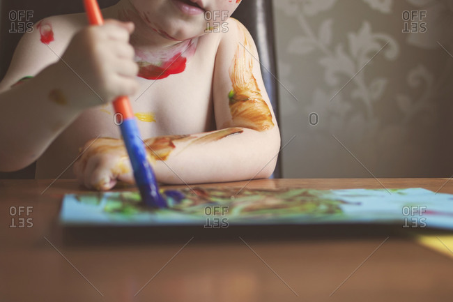 Child painting at table making mess