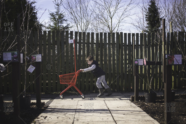 Boy running with cart in plant nursery