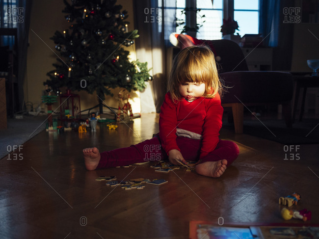 Girl putting puzzle together on floor