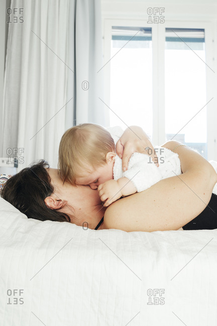 Mom napping with toddler on bed