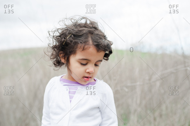 Young curly-haired toddler standing in grassy meadow