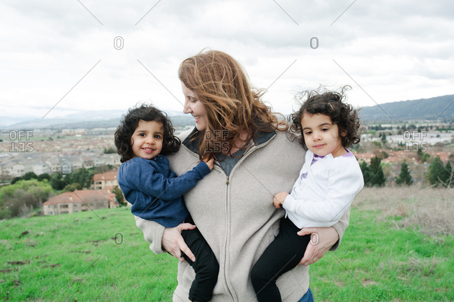 Woman holding her twins daughters on a hill above a town