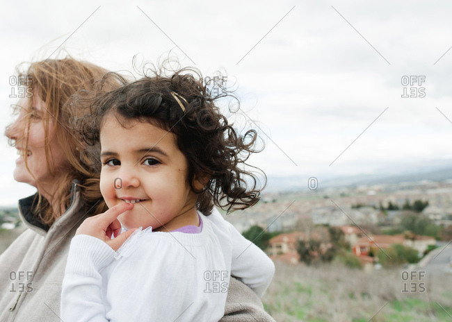 Woman holding her daughter in a breezy meadow above a town