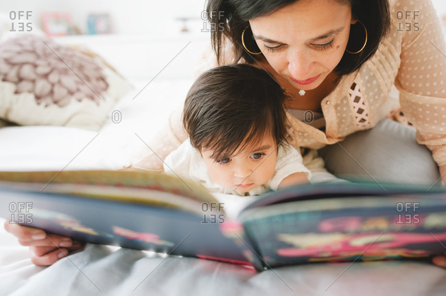 Woman reading a picture book with her young daughter