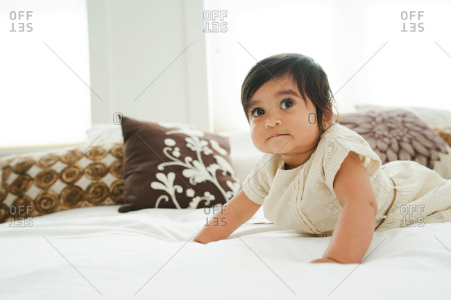 Baby with dark hair and dark eyes pushes herself up on a bed