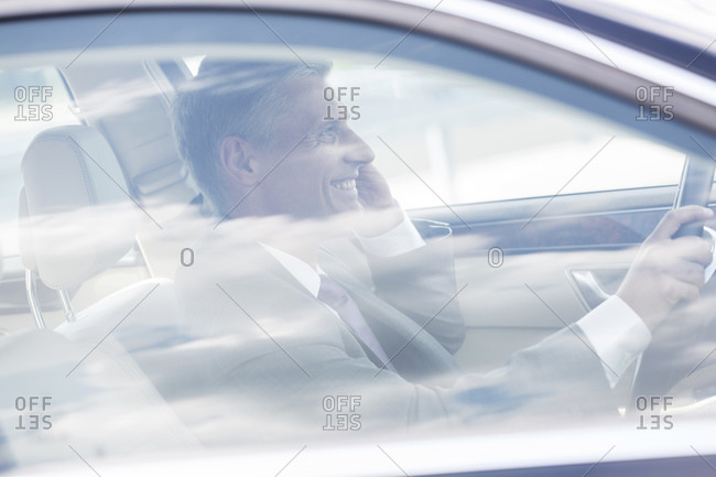 Smiling businessman on cell phone in car