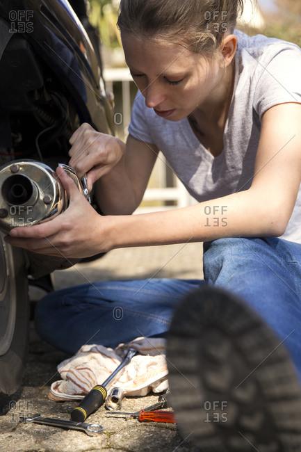 Woman repairing motor scooter
