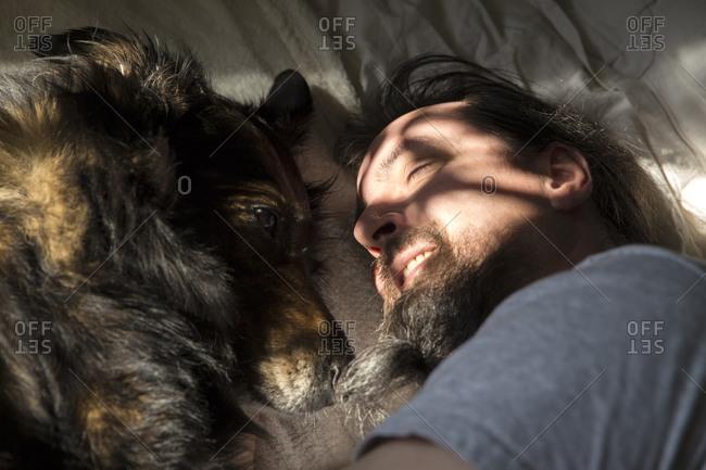 Man cuddling with mongrel dog