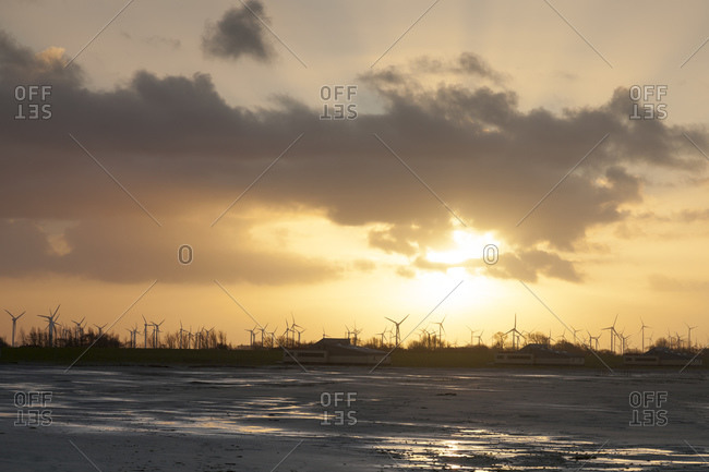 Coastal landscape with wind turbines at sunset