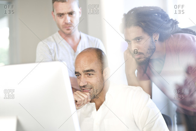 Three colleagues looking at screen in an office