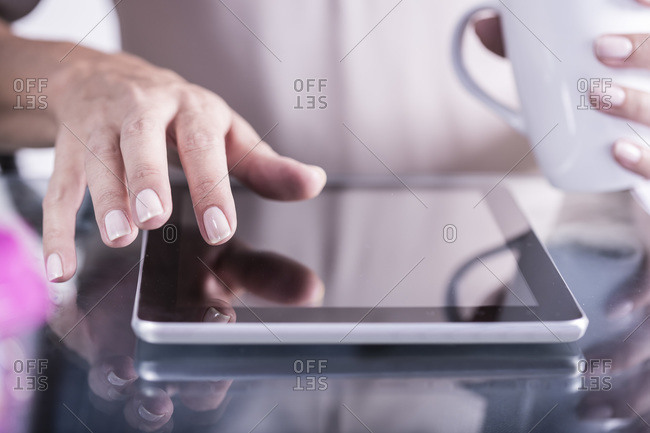 Woman drinking coffee and working on a tablet