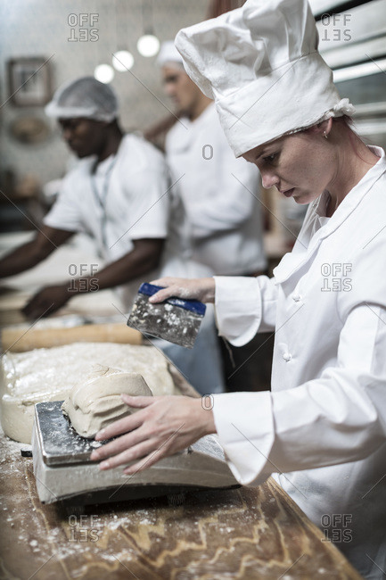 Female baker weighing dough and cutting it into correct sizes