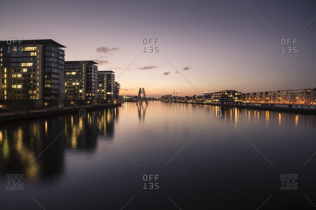 Berlin, Germany - March 2, 2015: Buildings and Molecule Man at River Spree in the evening