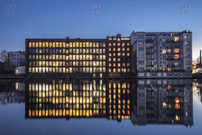 Berlin, Germany - March 2, 2015: Lighted office building and water reflections in the evening