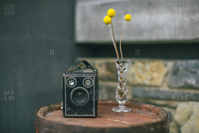 Still life view of a vintage box camera on a wooden cask