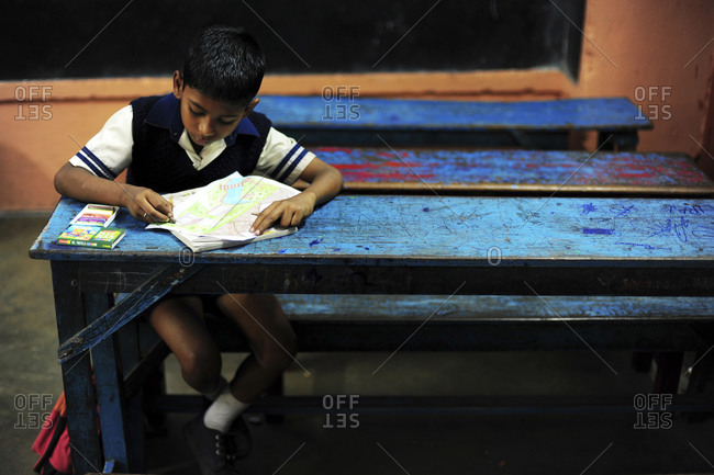 Young boy drawing at a table in Kolkota, India