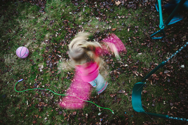 A little girl spins in her yard