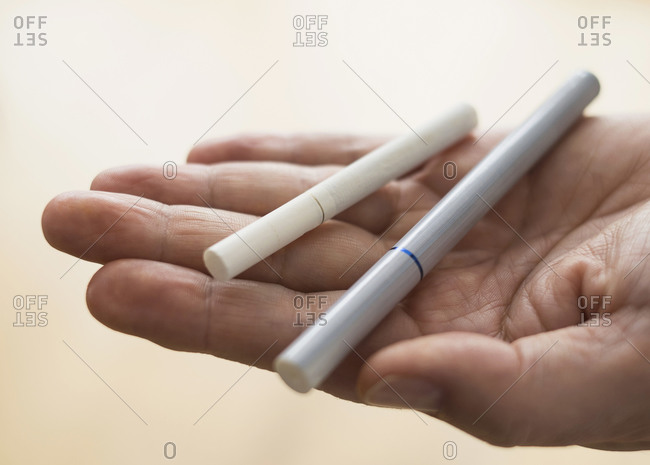 Close up of man's hand holding cigarette and e-cigarette
