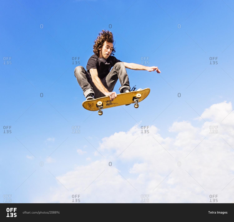 Man Grabbing Skateboard While Jumping Against Sky And