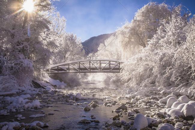 View of bridge over stream in winter