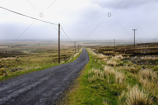 Rural country road runs through barren countryside