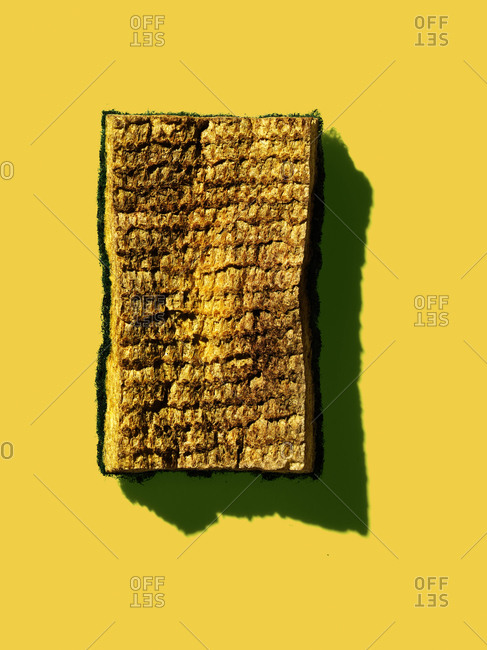 Dirty yellow sponge on a yellow background
