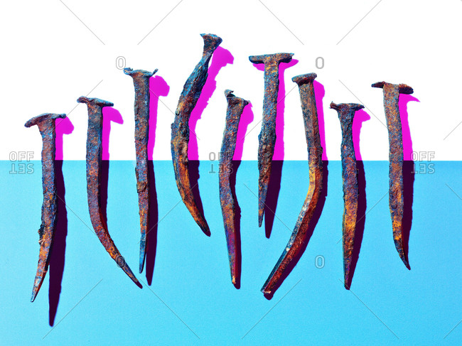Old rusty nails cast pink shadows on halved blue and white background
